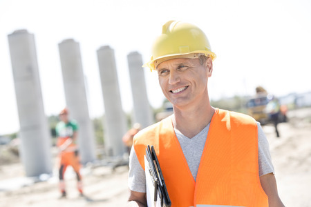 people: Happy architect looking away while holding clipboard at construction site