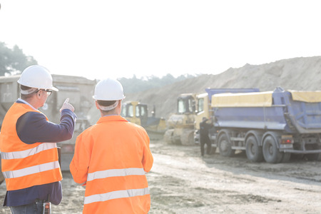 transportations: Supervisor explaining plan to colleague at construction site