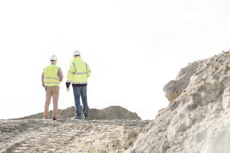 supervisores: Vista trasera de los supervisores permanente en obras de construcción contra el cielo claro