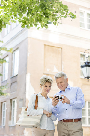 50s adult: Middle-aged couple reviewing photos on digital camera outside building LANG_EVOIMAGES