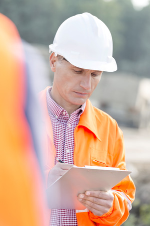 supervisor: Supervisor writing on clipboard at construction site LANG_EVOIMAGES