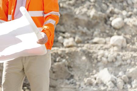 supervisor: Midsection of supervisor holding blueprint at construction site LANG_EVOIMAGES