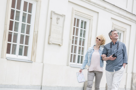 built in: Happy middle-aged tourist couple walking arm in arm by building