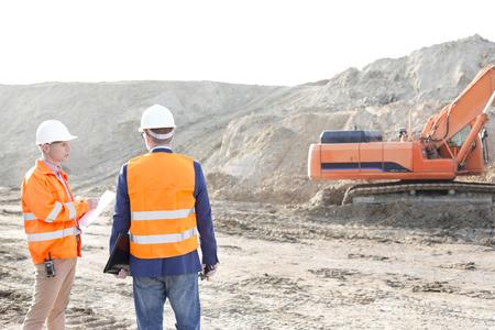 supervisores: Supervisores de pie en el sitio de construcción contra el cielo claro LANG_EVOIMAGES