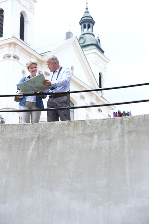 50s adult: Middle-aged couple reading map by railing outside church