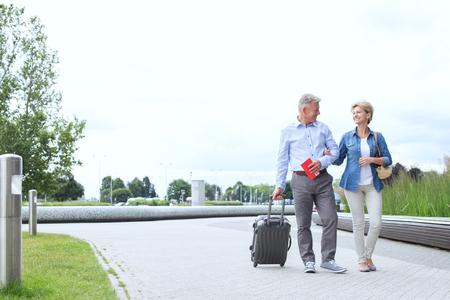 50s adult: Middle-aged couple with luggage walking on footpath against clear sky