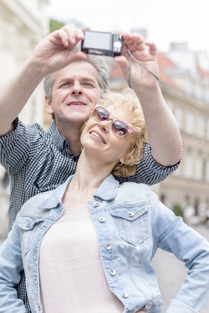 self   portrait: Happy middle-aged couple taking self portrait outdoors