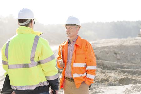 supervisores: Los supervisores que discuten en el sitio de construcción en día soleado