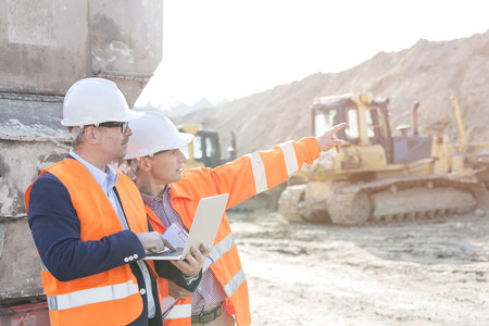 Supervisor showing something to coworker holding laptop at construction site Stockfoto