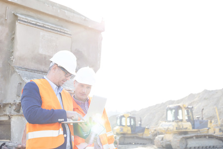 building contractor: Engineers using laptop at construction site against clear sky
