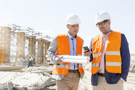 man on cell phone: Male engineers using mobile phone at construction site against clear sky