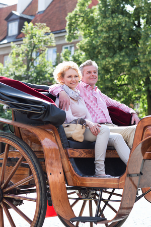 horse cart: Smiling middle-aged couple sitting in horse cart on city street LANG_EVOIMAGES