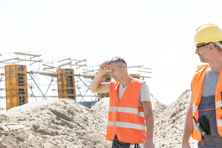exhausted worker: Construction worker looking at tired colleague wiping sweat at site