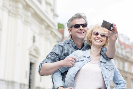 self   portrait: Happy middle-aged couple in sunglasses taking self portrait outdoors LANG_EVOIMAGES