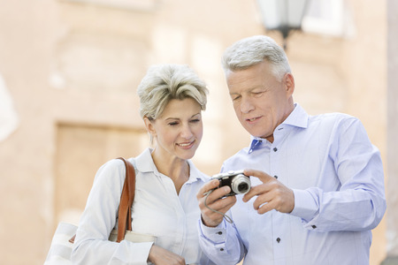 50s adult: Smiling middle-aged couple reviewing photos on digital camera outdoors