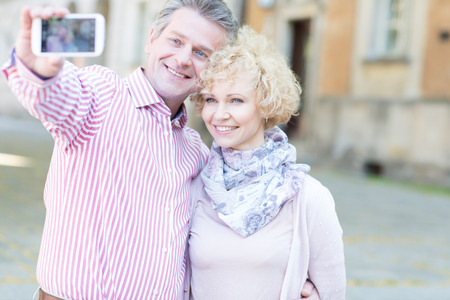 middleaged: Happy middle-aged couple taking selfie through smart phone in city LANG_EVOIMAGES