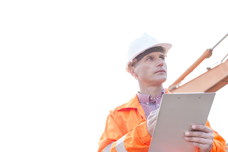 clear away: Supervisor looking away while holding clipboard against clear sky