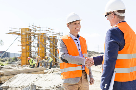 hands shaking: Engineers shaking hands at construction site against clear sky