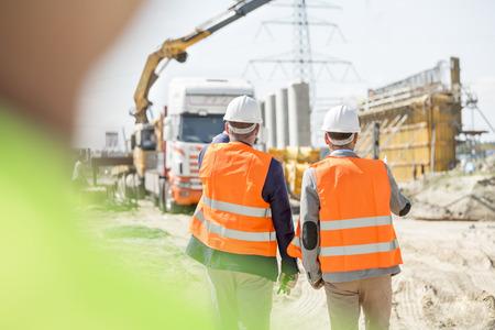 Vue arrière de superviseurs marchant au chantier de construction
