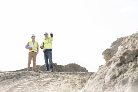 site manager: Supervisor discussing with colleague at construction site against clear sky