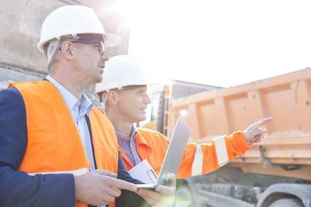 Supervisor muestra algo a su colega sosteniendo portátil en sitio de construcción