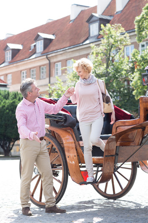 horse cart: Full-length of middle-aged man assisting woman out of horse cart