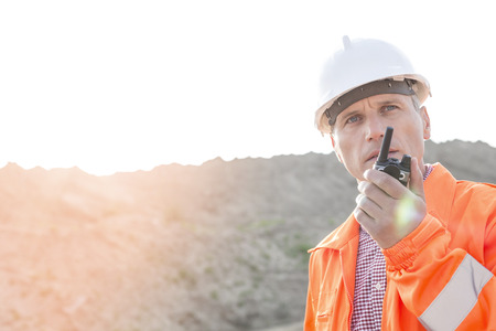 ���clear sky���: Confident supervisor using walkie-talkie on construction site against clear sky LANG_EVOIMAGES