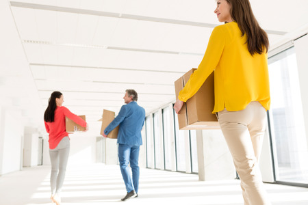 Rear view of business people with cardboard boxes moving into new office LANG_EVOIMAGES