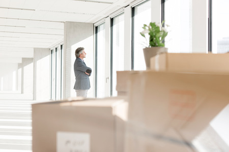 mid distance: Distant image of businessman looking through window with cardboard boxes in foreground