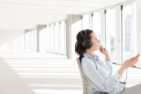 mid adult: Side view of mid adult businesswoman listening music through headphones in empty office