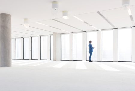 mid distance: Mature businessman visiting empty office space