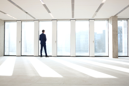 mid distance: Rear view of young businessman looking through office window