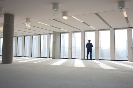 mid distance: Rear view of mature businessman visiting empty office space LANG_EVOIMAGES