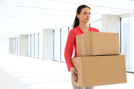 mid adult: Mid adult businesswoman carrying cardboard boxes in new office