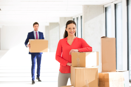 mid adult: Portrait of confident mid adult businesswoman standing by stacked boxes with male colleague in background at office
