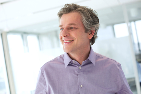 Smiling mature businessman looking away at office