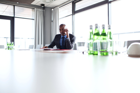 Young Businessman Using Mobile Phone At Conference Table Stock Photo - Mobile conference table