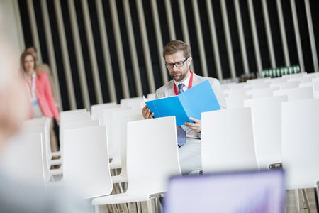 Convention Center: Businessman reading file while sitting in seminar hall at convention center LANG_EVOIMAGES