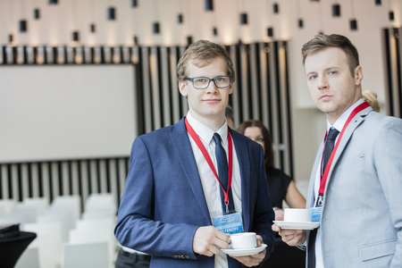 Convention Center: Portrait of confident businessmen holding coffee cups in convention center LANG_EVOIMAGES