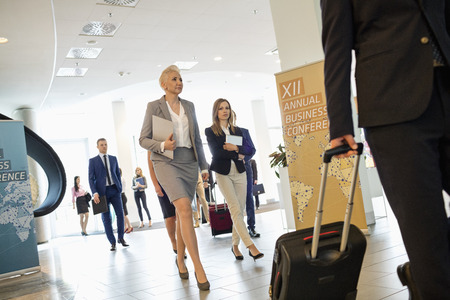 Convention Center: Business people pulling luggage while walking in convention center