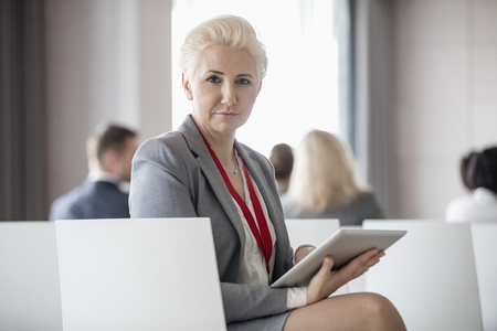 technology: Portrait of confident businesswoman holding digital tablet while sitting in seminar hall