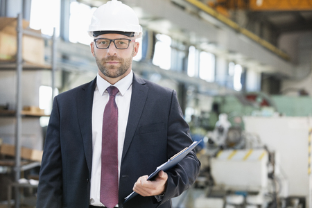 mid adult: Portrait of confident mid adult male supervisor holding clipboard in metal industry