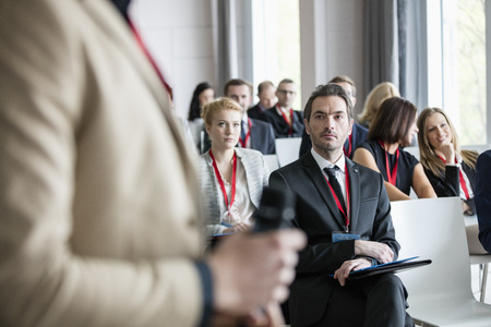 selective focus: Businessman looking at public speaker during seminar LANG_EVOIMAGES