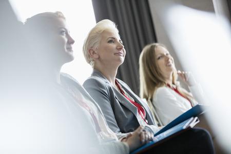 Smiling businesswomen attending seminar Stock Photo