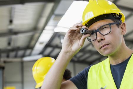 mid adult: Mid adult manual worker examining metal in industry