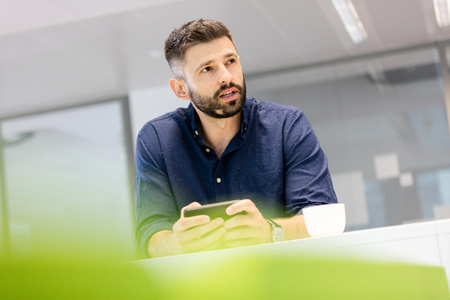mid adult: Mid adult businessman holding smartphone while looking away in office LANG_EVOIMAGES