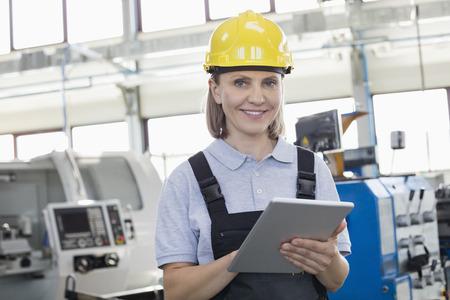 製造業のデジタル タブレットを使用して笑顔の女性労働者の肖像