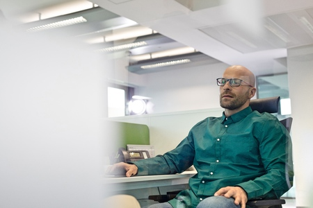 mid adult: Mid adult businessman sitting on chair in office
