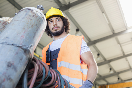 Low angle view of young manual worker moving gas cylinder in metal industry Banco de Imagens