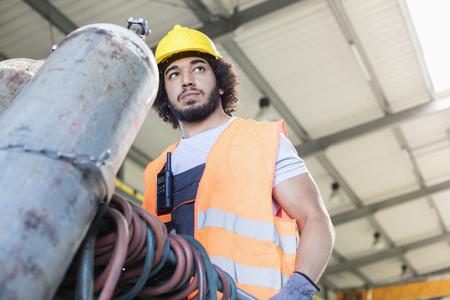 Vista baixa ângulo, de, jovem, trabalhador manual, em movimento, cilindro gás, em, metal, indústria Foto de archivo - 69411175